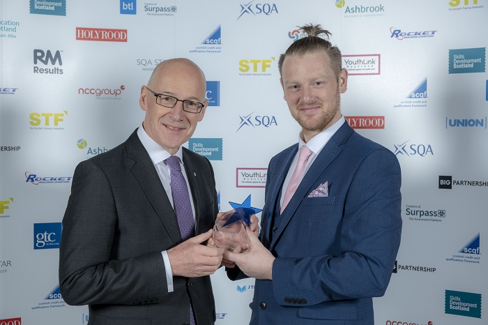 Dean Clark receiving award from John Swinney MSP