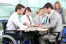 main in wheelchair and able bodied people sitting around table