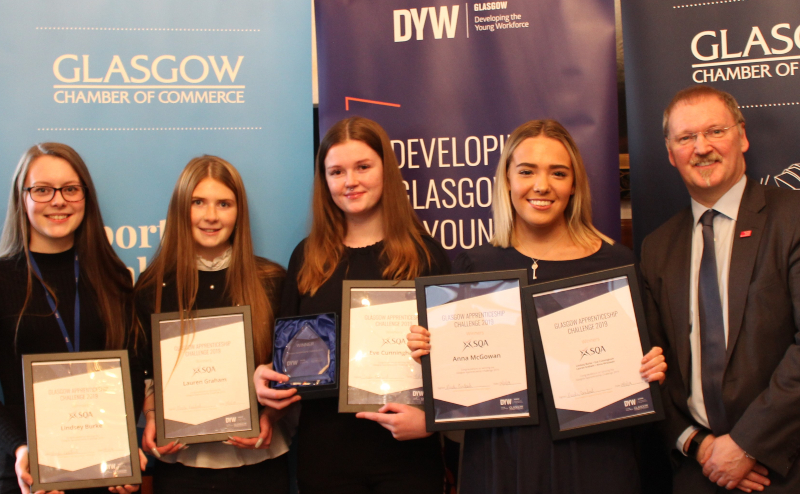 SQA's Modern Apprentices Lindsey Burke, Lauren Graham, Eve Cunningham, and Anna McGowan presented with a trophy by Stuart Patrick, Chief Executive of Glasgow Chamber of Commerce