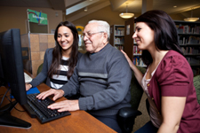 elderly man sitting at a computer supported by two women