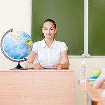 Test Administrator sitting at desk in classroom